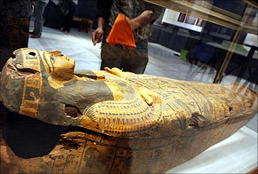 A worker in the Egyptian Museum cleans the display case of the Miami Coffin in Cairo