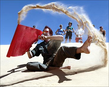 A tourist enjoys sand surfing near Dakhla oasis in Egypt's Western Desert .