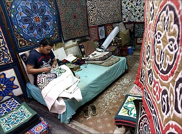 An Egyptian tentmaker sews in his shop during the Muslim fasting month of Ramadan, on the Street of the Tentmakers, in the historic quarter of Cairo.