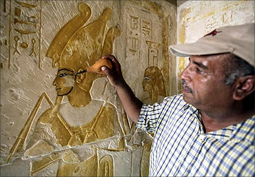 A worker blows dust off a mural in one of six tombs in the New Kingdom Cemetery in South Saqqara.