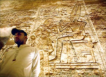 Man examines etchings inside temple of Abu Simbel at sunrise.