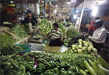 A customer (R) buys vegetables at a market in Ahmedabad.