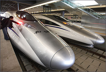A man looks at the bullet trains serving the high-speed railway linking Shanghai and Hangzhou in Sha