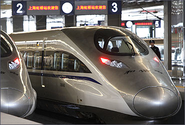 A policeman stands guard near the bullet trains serving the high-speed railway linking Shanghai and Hangzhou in Shanghai.