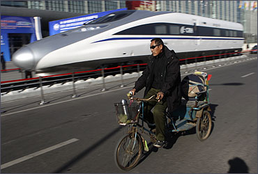 A Chinese resident rides a tricycle past the head of a CRH Harmony bullet train.