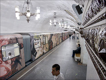 An underground train painted in a flower design enters Kievskaya station in Moscow.
