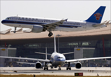 Air China plane waits on tarmac as a China Southern Airbus plane lands at Beijing Airport.