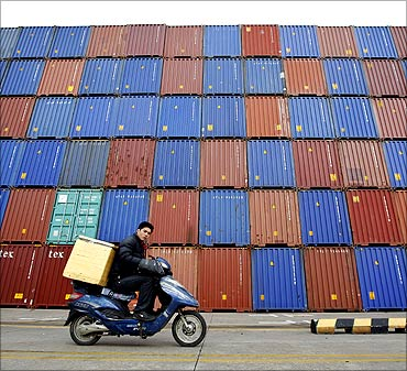 A man rides his motorcycle past shipping containers at the Port of Shanghai.