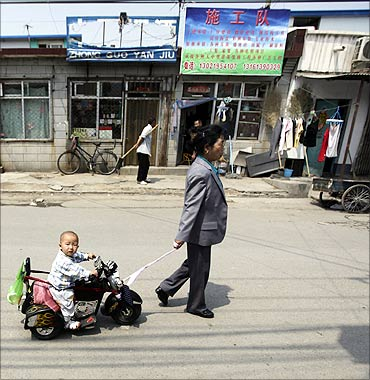 A woman pulls a toy ride carrying her grandson in a residential area for migrant workers.