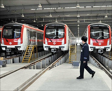 A driver walks in front of trains after testing a train at a metro station in Shenyang.