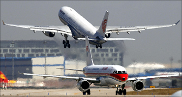 A China Eastern Airlines plane sits on the tarmac as an Air China plane takes off at Beijing Airport