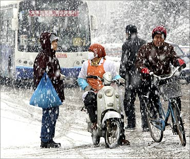 People make their way on a street amid snowfall in Yantai, Shandong province.