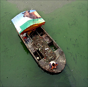 Workers on a boat collect trash from a polluted waterway in Beijing.