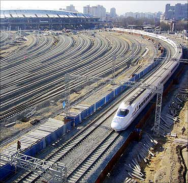 A bullet train departs from the under-construction Beijing South Railway Station.