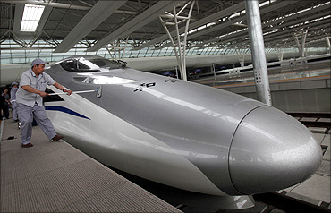 Workers clean the exterior of a CRH 380A bullet train.