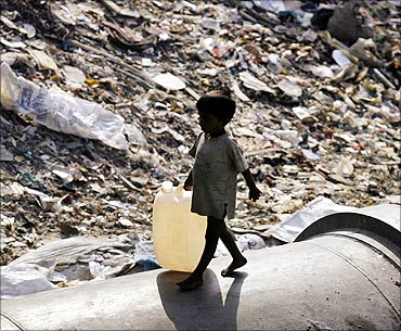 A boy carries a plastic container to fill water past a garbage dump in Mumbai.