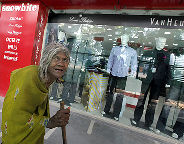 A beggar walks past a shop window.