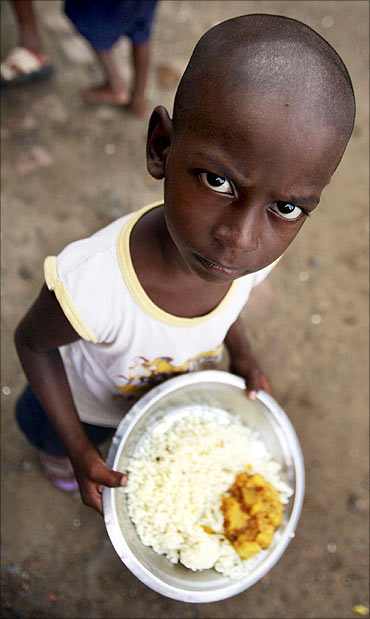 A student holds his free mid-day meal, distributed by a government-run primary school, in Rajpore.