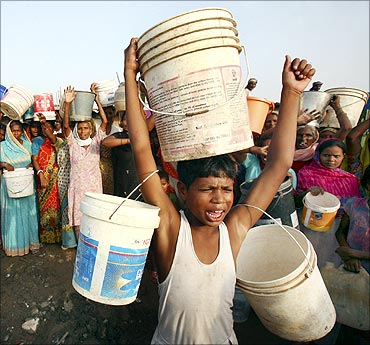 Slum dwellers shout slogans as they carry empty containers during a protest.