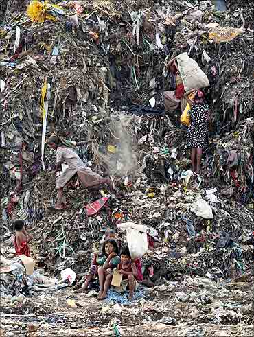 Children collect recyclable material at a dump in New Delhi