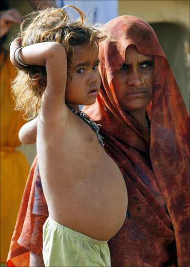 Four-year-old Kiran, who is suffering from malnutrition, stands next to her mother Sheil Rani in Balabehat village.