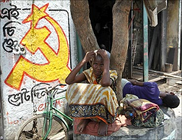 A woman sits under a tree next to a logo of the Communist Party of India.