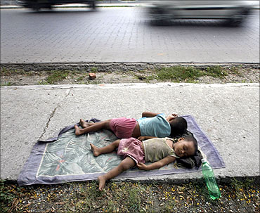 Homeless children sleep on the pavement beside a busy road.