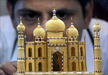 A worker displays a miniature 22 carat gold replica of the historic Taj Mahal.