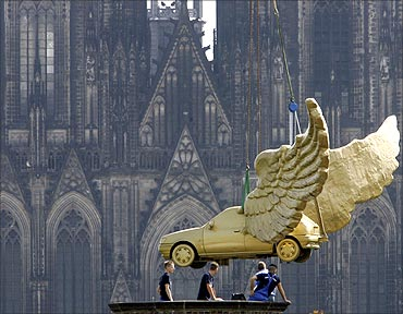 Workers install the sculpture 'Golden Bird' by German artist HA Schult in front of the cathedral.