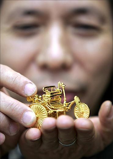 Taiwanese gold sculptor Jeng Ying-shie holds up a 108-gram mini gold sculpture of a Benz Motorwagen.