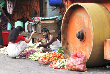 A vendor sells vegetables to a customer next to a parked road roller on a roadside in Kolkata.