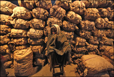 A vendor sits in front of sacks filled with potatoes at a wholesale vegetable market in Kolkata.