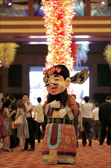 A man dressed as a Chinese God of Fortune walks inside the Resorts World Sentosa casino.