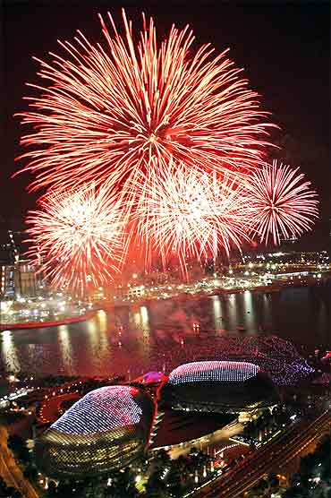 Fireworks explode over Marina Bay and the Esplanade theatres.