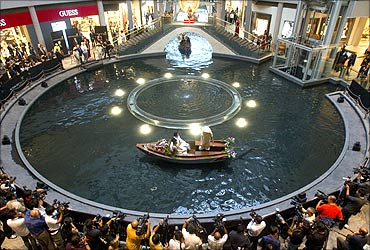 A newlywed couple takes a sampan ride on a canal inside a shopping centre at the Marina Bay Sands.