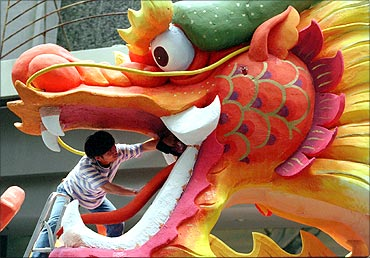 An artist puts finishing touches on a huge dragon display outside a Singapore shopping mall.