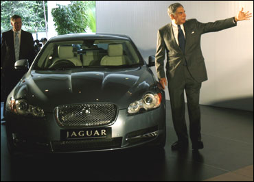 Ratan Tata gestures as he stands next to a Jaguar XF.