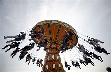 Visitors enjoy a ride at an amusement park in Noida,