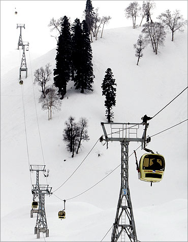 Foreign skiers travel in cable car gondolas in Gulmarg.