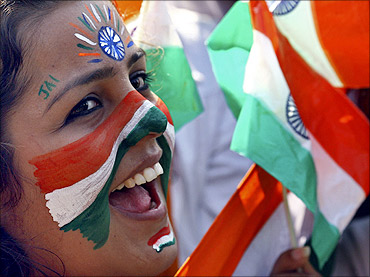 A college student cheers after getting her face painted with the tricolour Indian national flag.
