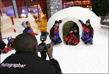 Children enjoy the snow in the mall.