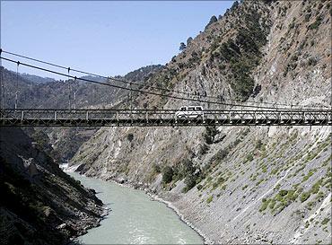A vehicle moves across a bridge on river Chenab.