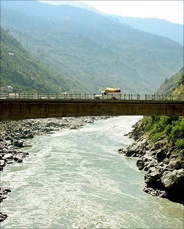 A vehicle moves through a bridge over river Chenab.