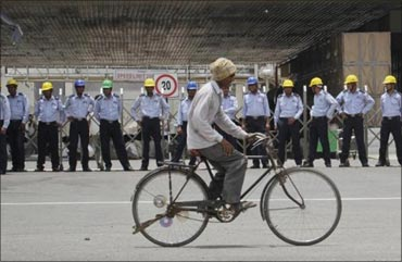 A man rides his bicycle infront of the Manesar plant.