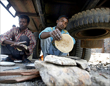 Labourers make roti under a truck at a roadside in Noida.