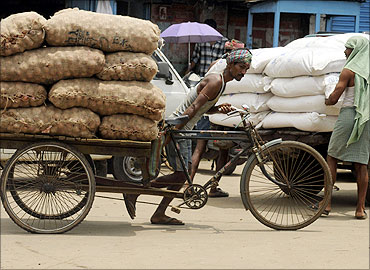 A rickshaw puller transports onions at a wholesale market in Agartala.