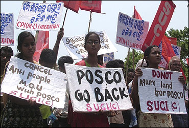 Villagers hold placards during a protest.