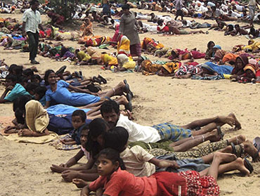 Villagers and their children lie at the proposed Posco site during a protest.