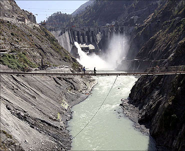 Labourers walk on a bridge near the hydropower project located at Baglihar Dam.
