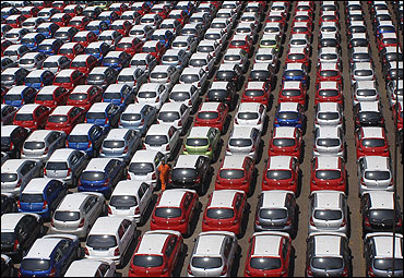 An employee walks between parked Hyundai cars ready for shipment.
